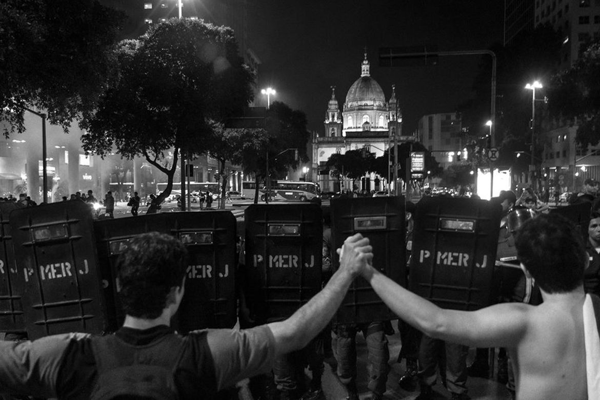 """Military Police officers confronting protesters during a protest in Presidente Vargas Avenue, Rio de Janeiro, in June 2013. In June 2013 huge demonstrations that took place in dozens of cities in Brazil through which people expressed their discontent with increased public transportation costs, high World Cup spending and insufficient investment in public services. The police response to the wave of protests in 2013 was, in many instances, violent and abusive. Military police units used tear gas indiscriminately against protesters, fired rubber bullets at people who posed no threat and beat people with hand-held batons. Hundreds were injured and hundreds more were indiscriminately rounded up and detained, some under laws targeting organized crime, without any indication that they were involved in criminal activity. In May 2014, Amnesty International launched the campaign """"No foul play, Brazil"""" warning about restrictions to freedom of expression and police abuses during protests and urging the authorities to ensure security forces """"play by the rules"""" during demonstrations expected to take place ahead and during the World Cup 2014."""